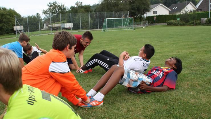 Die Jugendlichen wärmen sich fürs Fussballspiel auf.