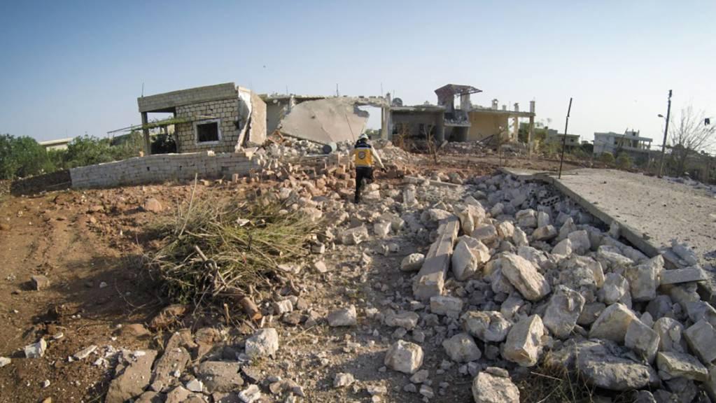 HANDOUT - Ein Mitglied des syrischen Zivilschutzes, bekannt als Weißhelm, steht inmitten von Trümmern von Häusern, die bei einem Luftangriff auf die Provinz Idlib zerstört wurden. Foto: Uncredited/Syrian Civil Defense White Helmets/AP/dpa - ACHTUNG: Nur zur redaktionellen Verwendung und nur mit vollständiger Nennung des vorstehenden Credits