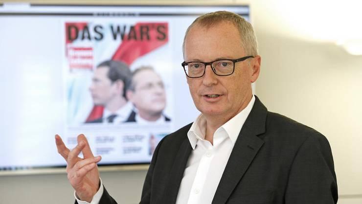 Krone-Chefredaktor Klaus Herrmann in seinem Büro in Wien. Hinter ihm die Frontseite der Sonntagsausgabe.