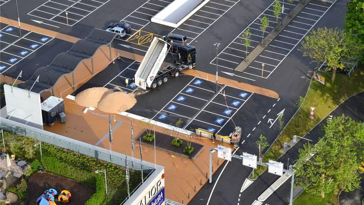 Einer der drei Lastwagen kippt seinen Teil der insgesamt 110 Tonnen Sand auf den Parkplatz vor dem Shoppi-Eingang in Spreitenbach.ZVG