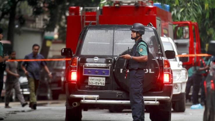 Polizisten riegeln das Gebiet ab, in dem der Angriff geschah - laut der Regierung gehörten die Angreifer auf ein Café in Dhaka einer lokalen Islamistenorganisation an.