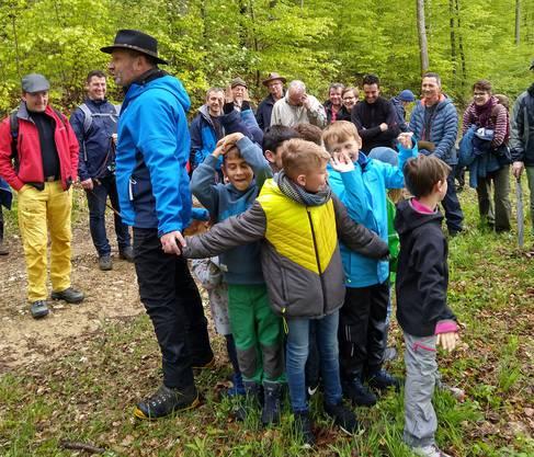 Der Förster zeigt mit den Kindern zusammen wie ein Baum funktioniert.