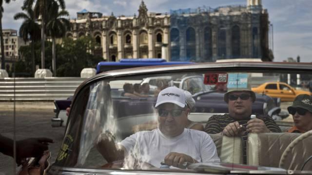 Touristen sitzen in einem amerikanischen Oldtimer in Havanna, Kuba