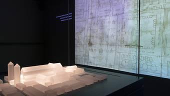 """Ein Modell des St. Galler Klosters, links, und eine Projektion des Planes, in der Ausstellung """"Das Wunder der Überlieferung – Der St.Galler Klosterplan und Europa im frühen Mittelalter"""" in St. Gallen."""