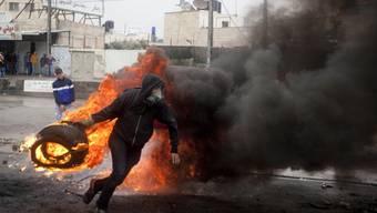 Ein Palästinenser wirft bei Ramallah einen brennenden Reifen