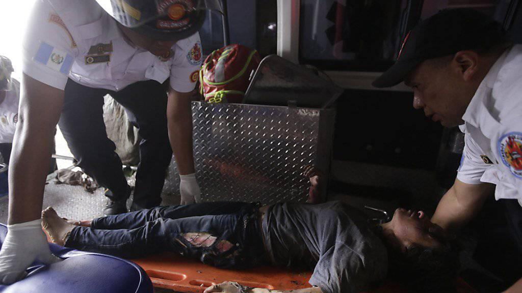 Nach einem Brand in einem Kinderheim in Guatemala wird ein Mädchen mit Verbrennungen ins Spital gebracht - mindestens 29 Mädchen kamen in den Flammen um.