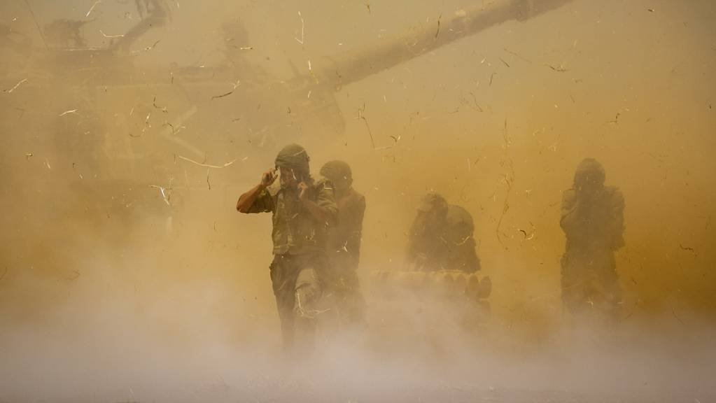 dpatopbilder - Israelische Soldaten stehen in aufgewirbeltem Staub, nachdem ein Artilleriegeschütz auf Ziele im Gazastreifen gefeuert hat. Foto: Yonatan Sindel/AP/dpa