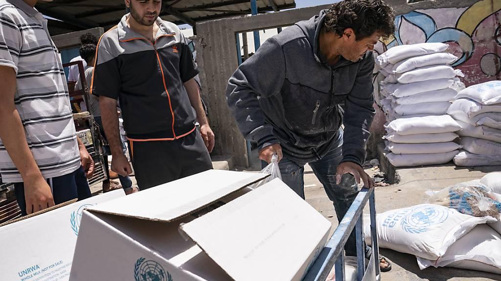 Helfer tragen Säcke mit Lebensmitteln. Foto: John Minchillo/AP/dpa