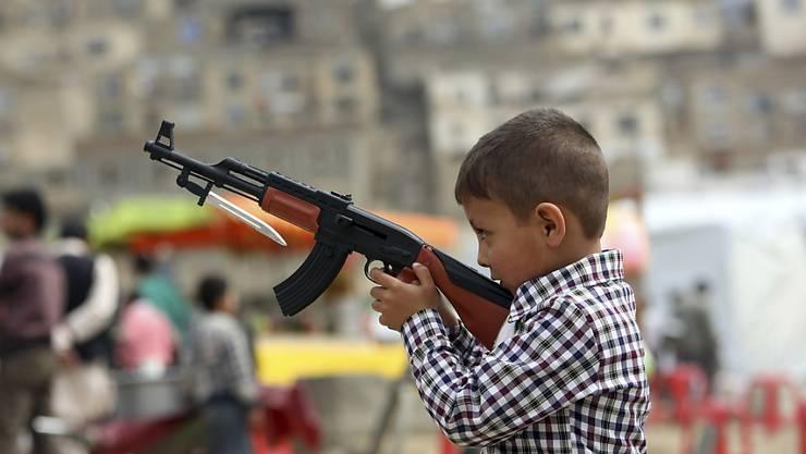 ein afghanischer Junge spielt während der Feiern zum persischen Neujahr mit einem Spielzeuggewehr (Archiv)