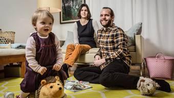 Emma (1) mit Igel, Madeleine (33) und Stefan (29) sitzen im Wohnzimmer in Aarau und warten auf das neue Jahr.