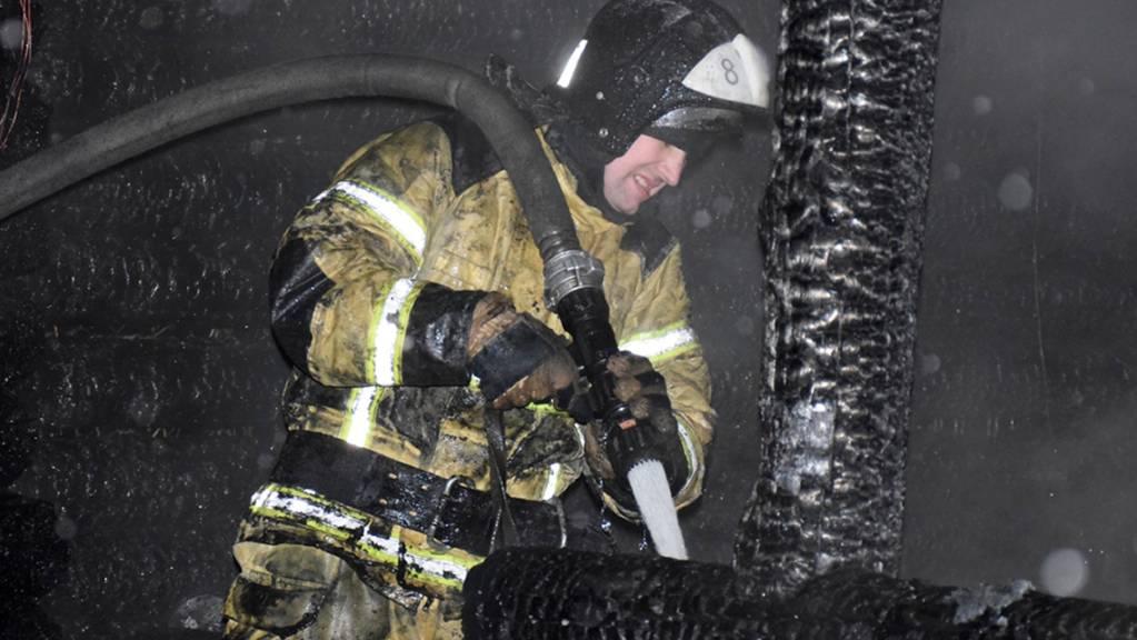HANDOUT - Ein Feuerwehrmann am Brandort an einem Altenheim. Foto: Uncredited/Russian Emergency Ministry Press Service/AP/dpa - ACHTUNG: Nur zur redaktionellen Verwendung und nur mit vollständiger Nennung des vorstehenden Credits