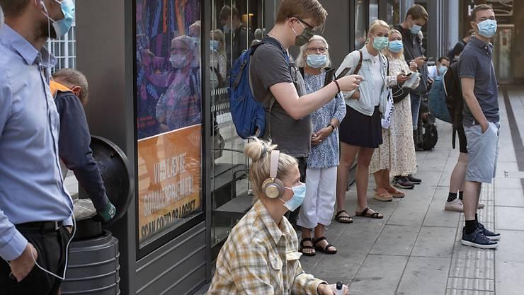 Fahrgäste tragen Mundschutze und warten in Aarhus auf einen Zug. Einwohner und Touristen in der dänischen Kommune müssen nach einem Corona-Ausbruch ab dem 11.08.2020 vorübergehend im öffentlichen Nahverkehr Mundschutz tragen. Die Maßnahme gilt vorläufig für drei Wochen. Foto: Bo Amstrup/Ritzau Scanpix Foto/AP/dpa