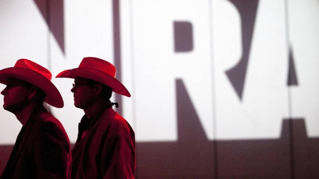 ARCHIV - Zwei Personen gehen an einem Schriftzug der NRA vorbei. Foto: Johnny Hanson/Houston Chronicle/AP/dpa - ACHTUNG: Nur zur redaktionellen Verwendung und nur mit vollständiger Nennung des vorstehenden Credits