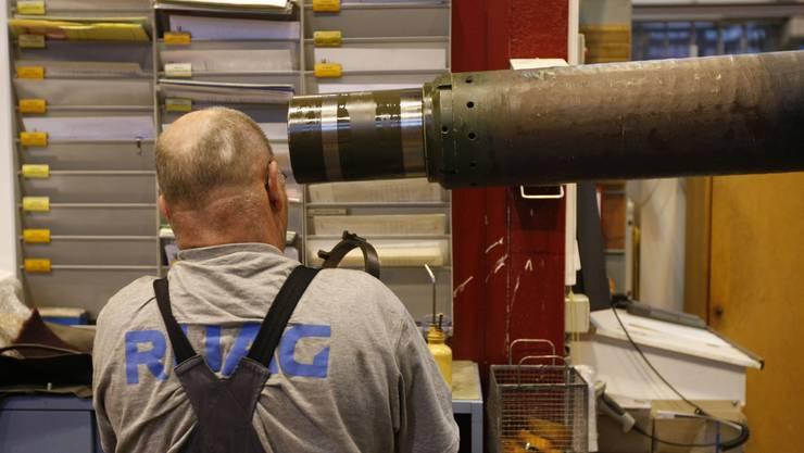 Ein Arbeiter bei Werterhaltungsarbeiten am Geschützrohr eines Leopard-Panzers in den Produktionshallen der Ruag. (Archiv)