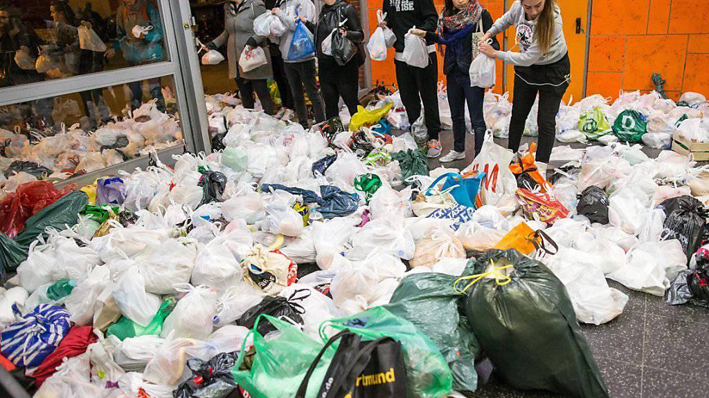 Freiwillige Helfer verteilen in einer Menschenkette Hilfspakete an ankommende Flüchtlinge im Zentralbahnhof von Dortmund