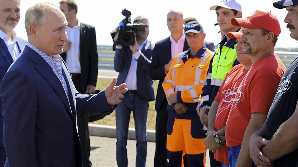 Wladimir Putin (2.v.l), Präsident von Russland, spricht bei der Eröffnungszeremonie der Tavrida-Autobahn auf der Krim, die Kertsch und Sewastopol verbindet, mit Arbeitern. Foto: Mikhail Klimentyev/Pool Sputnik Kremlin/AP/dpa