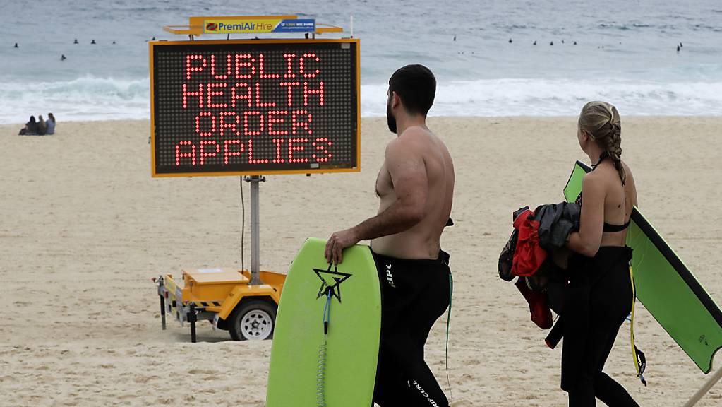 Ein Schild weist Menschen an einem Strand in Sydney auf Einschränkungen hin.