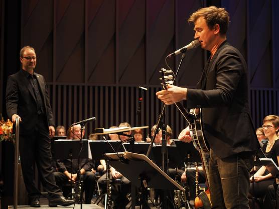 Zwei Männer vor  grossem Orchester - Dirigent Christian Noth (links) und Gustav