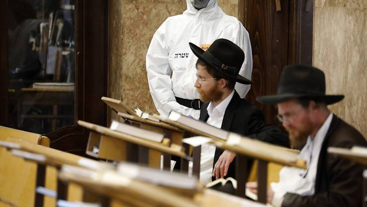 Ein israelischer Polizeibeamter betrachtet zwei orthodoxe Juden in einer Synagoge in Tel Aviv. (Archivbild)