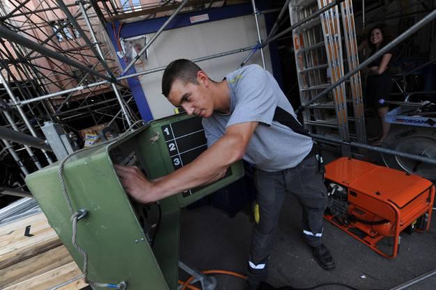 Der Arbeiter Karim Sadok kümmert sich um die Zuleitung der Lichtinstallationen unter der Tattoo-Tribüne.
