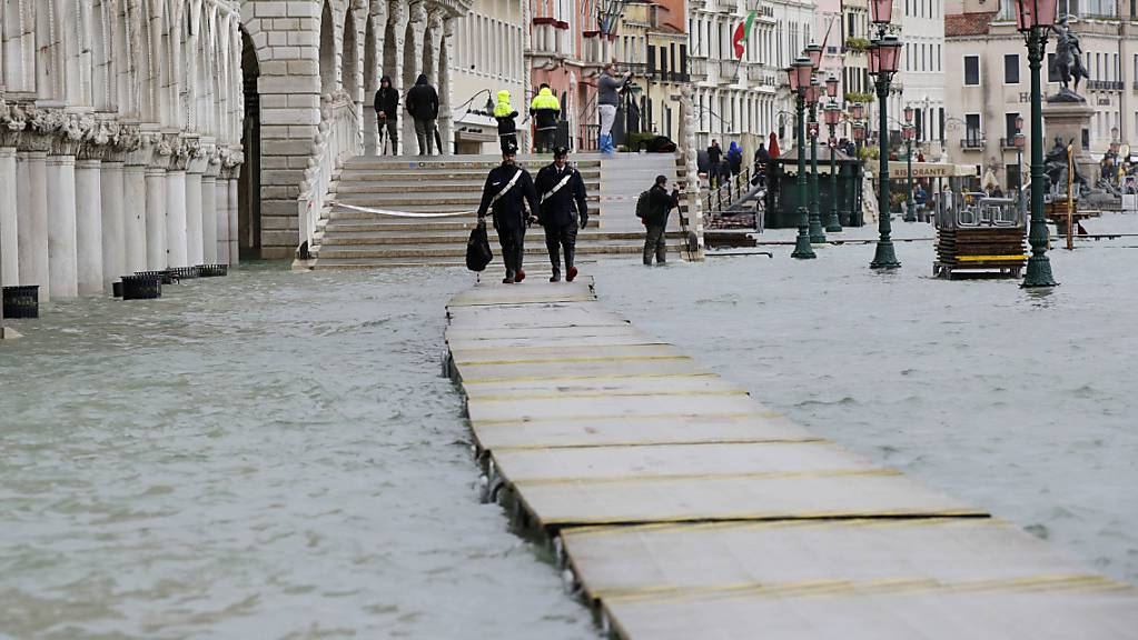Zwei Carabinieri auf einem Steg im überfluteten Venedig.