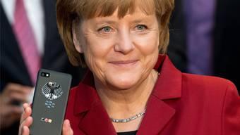 Merkel präsentiert stolz ihr ahörsicheres Handy (Archivbild).