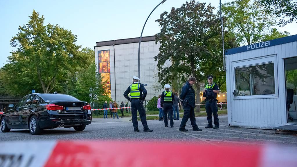 Mehrere Polizeibeamte und Zivilisten stehen im abgesperrten Bereich vor der Synagoge in Hamburg-Harvestehude.