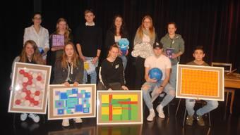 Einige der Preisträgerinnen und Preisträger posieren mit ihren Werken.