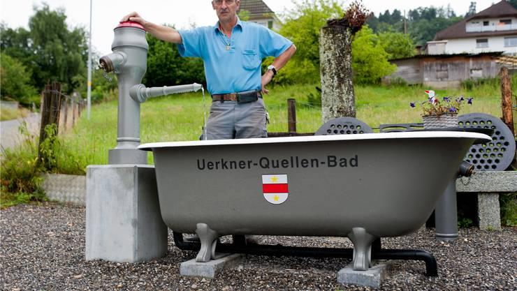 Brunnenmeister Werner Siegrist vor einem Quellwasser-Spender, den er und Kollegen in Fronarbeit erstellt haben. bkr