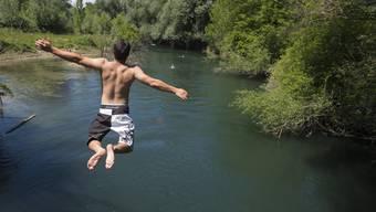 Ein junger Mann springt in die Limmat beim Limmatspitz zwischen Brugg und Turgi.