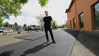 Der Künstler Kilian Rüthemann begeht den zweiten Teil seines Aussenprojekts «Run»: Den schwarzen Teppich, der zum Kunsthaus Baselland führt.