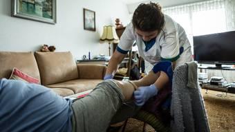 Eine Mitarbeitende der Spitex kümmert sich um einen Patienten. (Symbolbild)