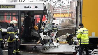 Nach dem Zusammenstoss eines Linienbusses mit einem Lastwagen in Hamburg untersuchen Einsatzkräfte die Unfallstelle.