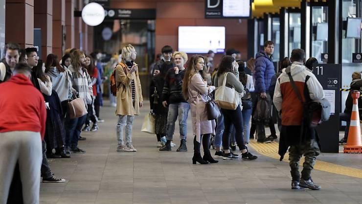 Pendler warten an einem Busbahnhof. In Neuseeland gibt es wieder Coronavirus-Fälle. Foto: Mark Baker/AP/dpa