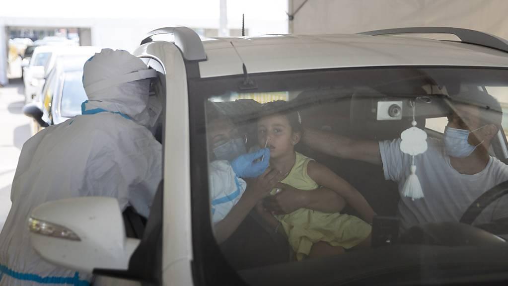 Ein medizinischer Mitarbeiter entnimmt einem Mädchen an einer Drive-Thru-Station für Covid-19-Tests einen Abstrich über die Nase. Nach einem deutlichen Anstieg von Corona-Neuinfektionen hat Israel am Montag die Beschränkungen zur Eindämmung des Virus verschärft.