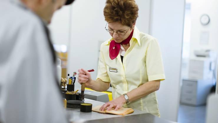 """Immer weniger """"Gelbe Büchlein"""" der Post: Eine Sachlterangestellte der Post in Sursee LU nimmt 2007 Einzahlungen entgegen. (Archivbild)"""