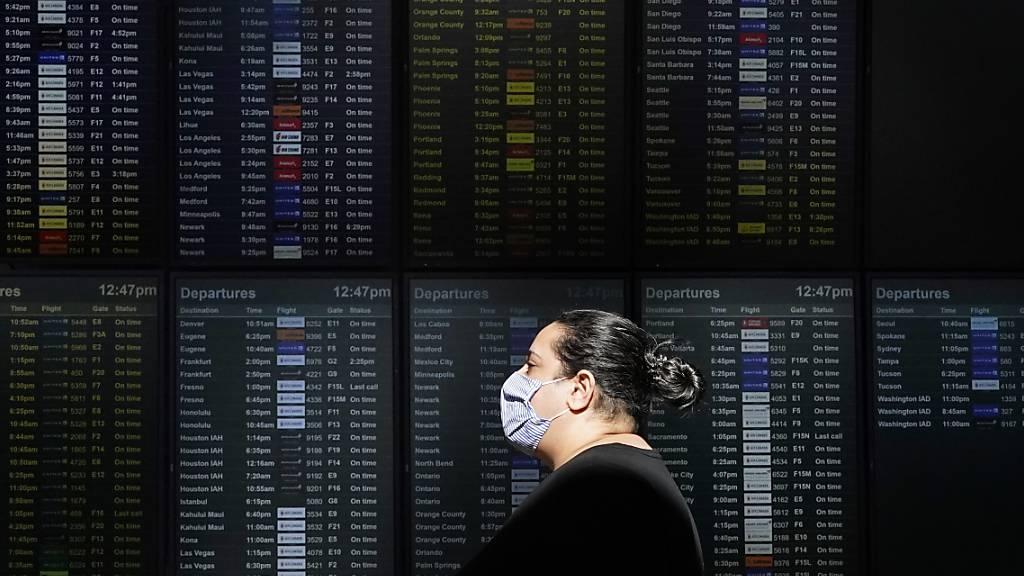ARCHIV - Eine Frau mit Mund-Nasen-Schutz geht an einer Anzeigetafel am Internationalen Flughafen von San Francisco vorbei. Foto: Jeff Chiu/AP/dpa