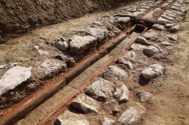 Die Leitung im Wohnquartier besteht aus aneinander gefugten Leistenziegeln. Sie sind mit Mörtel (rote Masse) befestigt und in Kalkbruchsteinen eingelassen.