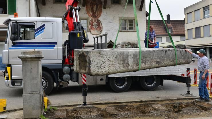 Der Brunnen wird mit den Traggurtschlaufen gesichert, mit dem Kran hochgehoben und zum Wegtransport auf den Lastwagen verladen. Bruno Kissling
