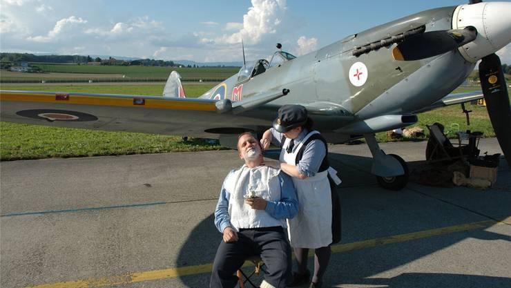 Mit der blanken Klinge rückt die Angehörige der Women's Auxiliary Airforce (WAAF) vor der Spitfire dem Bart des Corporals zu Leibe.