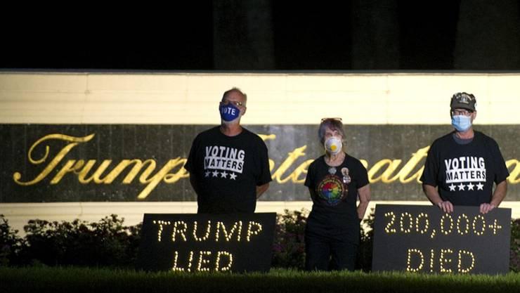 Die Demonstranten Mark Beaumont (l-r), Joyce Brown und Bruce Brown halten in der Nähe des Trump International Golf Club eine Mahnwache ab. In den USA sind inzwischen fast 200 000 Menschen nach einer Corona-Infektion gestorben. Foto: Meghan Mccarthy/Palm Beach Post via ZUMA Wire/dpa