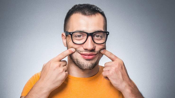 Mann zieht Mundwinkel hoch