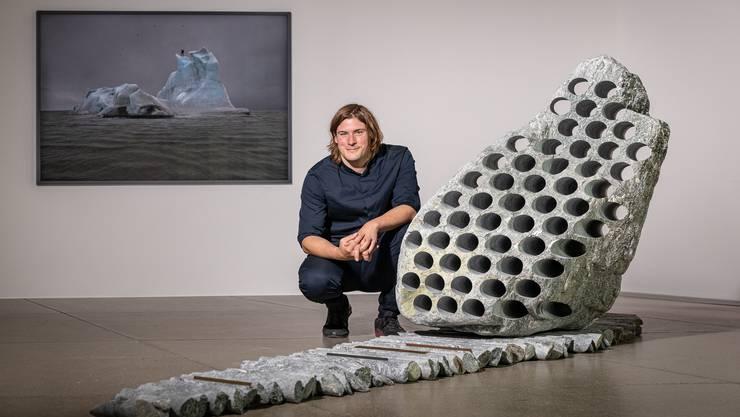 Julian Charrière mit einem aufgebohrten Findling aus dem Maggiatal im Aargauer Kunsthaus. Das Foto dahinter zeigt, wie er einen Eisberg mit einem Bunsenbrenner traktiert.