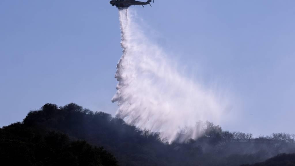 Ein Hubschrauber wirft Wasser ab, um Brandherde in einem Waldbrand in Topanga, westlich von Los Angeles, zu löschen. Die Rauchschwaden der heftigen Waldbrände an der US-Westküste trüben die Aussichten an der knapp 4000 Kilometer entfernten Ostküste. Foto: Ringo H.W. Chiu/AP/dpa