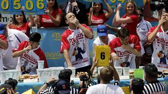 Der Serien-Champion Joey Chestnut (Mitte)  verbesserte er seinen Rekord vom Vorjahr um zwei Hotdogs.