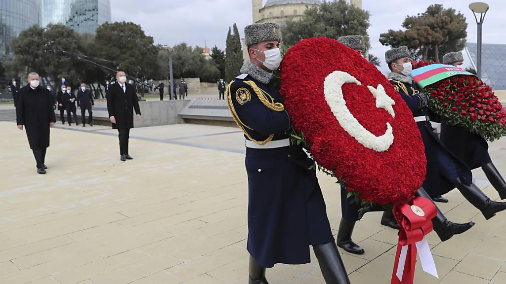 Recep Tayyip Erdogan (hinten, l), Staatspräsident der Türkei, und Ilham Alijew (hinten, r), Präsident von Aserbaidschan, nehmen an einer Kranzniederlegung teil. Zuvor waren sie bei einer Militärparade, mit der Aserbaidschan seinen «Sieg» im Krieg um die Südkaukasus-Region Berg-Karabach feierte. Foto: -/Turkish Presidency/AP/dpa