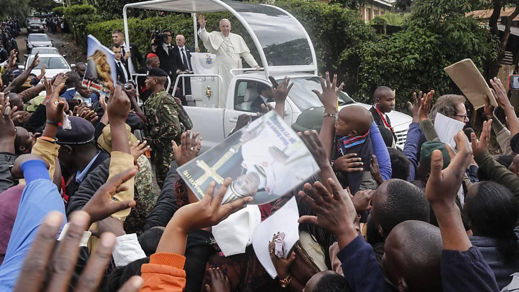 Im offenen Papamobil fährt der Papst durch Kangemi. In seiner Rede verurteilt er anschliessend, dass viele Menschen durch Ungerechtigkeit und Profitgier in die Armut getrieben werden.