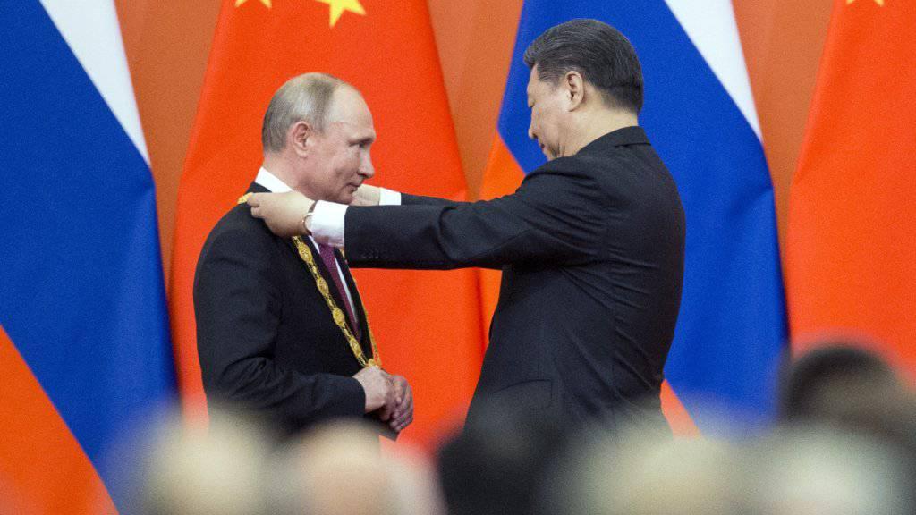 Chinas Präsident Xi Jinping ehrt seinen Gast aus Russland, Wladimir Putin, mit der erstmals verliehenen goldenen Ehrenmedaille.