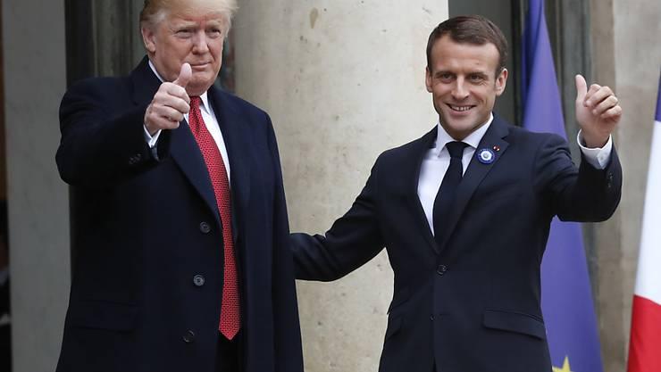 Lächeln vor den Kameras - nach bissigem Tweet: US-Präsident Trump (links) mit dem französischen Präsidenten Macron in Paris.