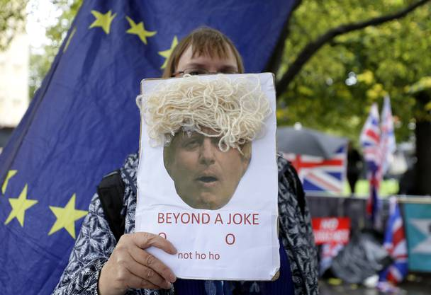 An anti-Brexit demonstrator holds a placard near Parliament in London, Thursday, Oct. 17, 2019. UK Prime Minister Boris Johnson on Thursday departed Downing Street to head to a crunch EU summit, after European Union and British negotiators agreed on an outline Brexit deal. (AP Photo/Kirsty Wigglesworth)